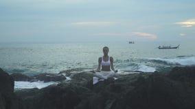 Praktiserande yoga för kvinna på havsstranden stock video