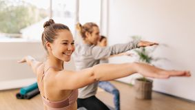 Praktiserande yoga för kvinna på idrottshallgrupp Royaltyfri Fotografi