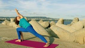 Praktiserande yoga för kvinna på stranden på solnedgången arkivfilmer