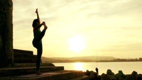 Praktiserande yoga för kvinna på stranden på solnedgången stock video