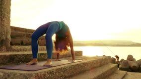 Praktiserande yoga för kvinna på stranden på solnedgången lager videofilmer
