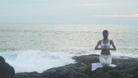 Praktiserande yoga för kvinna som poserar på stranden arkivfilmer