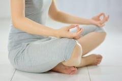 Praktiserande yoga för kvinna som sitter i en Lotus Pose And Meditating Arkivbild