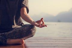 Praktiserande yoga för kvinna vid en sjö arkivbild