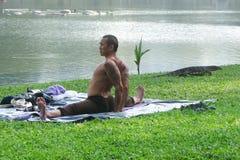 Praktiserande yoga för man i parkera Royaltyfria Foton