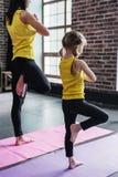 Praktiserande yoga för moder som och för dotter mediterar tillsammans att stå på ett ben med händer i bön arkivfoto