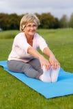 Praktiserande yoga för mogen kvinna i parkera Royaltyfri Fotografi