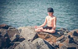 Praktiserande yoga för pojke på stranden fotografering för bildbyråer