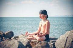 Praktiserande yoga för pojke på stranden Arkivbilder