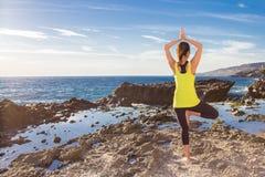 Praktiserande yoga för sund asiatisk kvinna på den bärande gulingöverkanten för strand Royaltyfria Bilder