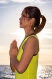 Praktiserande yoga för sund asiatisk kvinna på den bärande gulingöverkanten för strand Royaltyfri Foto