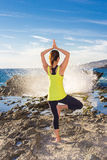 Praktiserande yoga för sund asiatisk kvinna på den bärande gulingöverkanten för strand Royaltyfri Fotografi