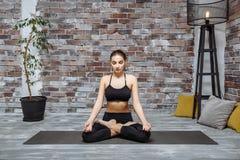 Praktiserande yoga för ung attraktiv kvinna hemma och att sitta i Padmasana Lotus poserar Arkivbilder
