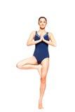 Praktiserande yoga för ung gladlynt kvinna som balanserar i trädposition Arkivbild