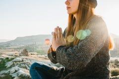 Praktiserande yoga för ung härlig flicka upptill av ett berg i Cappadocia på soluppgång Övningar av avkoppling arkivfoto