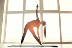 Praktiserande yoga för ung härlig kvinna och gymnastiskt Wellnessbegrepp Grupper i enkla sportar Arkivbild