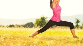 Praktiserande yoga för ung idrotts- kvinna på en äng på solnedgången Arkivbilder