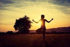 Praktiserande yoga för ung idrotts- kvinna på en äng på solnedgången Royaltyfri Fotografi