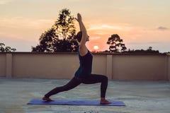 Praktiserande yoga för ung idrotts- kvinna på taket på solnedgången, silh Royaltyfri Foto