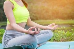 Praktiserande yoga för ung konditionkvinna på fältet, sund mest lifest arkivbild
