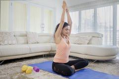 Praktiserande yoga för ung kvinna hemma fotografering för bildbyråer