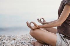 Praktiserande yoga för ung kvinna nära havet Harmoni, meditation och loppbegrepp Sund livsstil royaltyfri fotografi