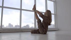 Praktiserande yoga för ung kvinna och upp sträckningsben arkivfilmer