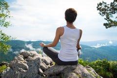 Praktiserande yoga för ung kvinna på en bergöverkant Royaltyfria Bilder
