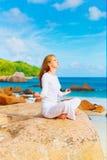 Praktiserande yoga för ung kvinna på vagga Royaltyfri Bild