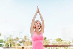 Praktiserande yoga för ung kvinna utomhus Arkivbild