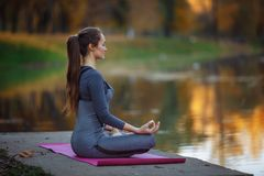 Praktiserande yoga för ung kvinna utomhus Kvinnlign mediterar utomhus- i framdel av den härliga höstnaturen royaltyfria foton