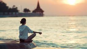 Praktiserande yoga för ung sund kvinna på stranden på solnedgången stock video