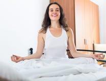 Praktiserande yoga för flicka i säng Royaltyfria Foton