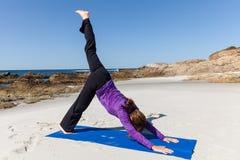 Praktiserande yoga på stranden Arkivfoton