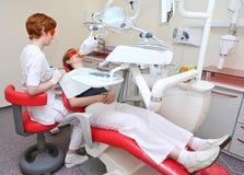 Praktizierender Zahnarzt im zahnmedizinischen Raum lizenzfreies stockbild