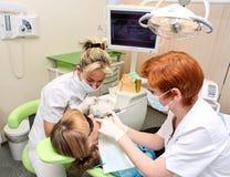 Praktizierender Zahnarzt im zahnmedizinischen Raum stockbild