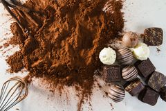 PRALINE CHOCOLATE IN CACAO POWDER. HOMEMADE CHOCOLATE IN WORK WITH EGG BEATER AND VANILLA BEAN ON WHITE BACKGROUND. STILL LIFE SWEET. KITCHEN WORK Royalty Free Stock Photo