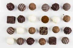 PRALINE CHOCOLATE IN CACAO POWDER SPLASH. HOMEMADE CHOCOLATE IN WORK WITH VANILLA BEAN ANS CINNAMON ON WHITE BACKGROUND. PRALINE CHOCOLATE IN CACAO POWDER Stock Images