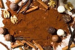 PRALINE CHOCOLATE IN CACAO POWDER SPLASH. HOMEMADE CHOCOLATE IN WORK WITH VANILLA BEAN ANS CINNAMON ON WHITE BACKGROUND. PRALINE CHOCOLATE IN CACAO POWDER Stock Photo