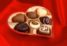 Praline del cioccolato in scatola dorata su seta rossa Immagine Stock Libera da Diritti