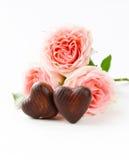 Praline in Form der Herzen und der rosa Rosen für Valentinstag Stockfotos