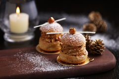 Praline hazelnut choux on wooden tray with pine for Christmas stock image