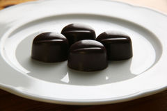 Praline laying on a plate.JH. Four brown chocolate pralines laying on a white plate stock images