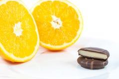 Pralinen mit orange Creme beschichteten in der glatten dunklen Schokolade auf Platte Stockbild