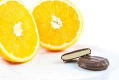 Pralinen mit orange Creme beschichteten in der glatten dunklen Schokolade auf Platte Stockfotografie
