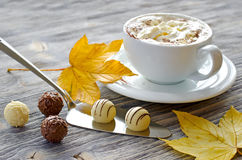 Pralines, a cup of cappuccino and autumn leaves. Chocolate pralines on wooden background selective focus Royalty Free Stock Photos