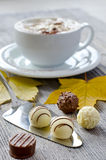 Pralines and a cup of cappuccino. Chocolate pralines on wooden background selective focus Royalty Free Stock Image