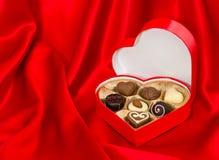 Pralines de chocolat dans le cadre d'or au-dessus de la soie rouge Images libres de droits