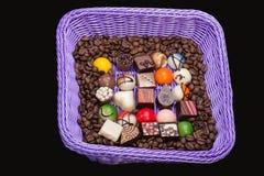 Pralines de chocolat et grains de café dans le panier de lavande Images stock