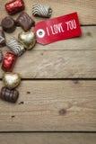Pralines et signe rouge je t'aime sur le fond en bois Photographie stock libre de droits
